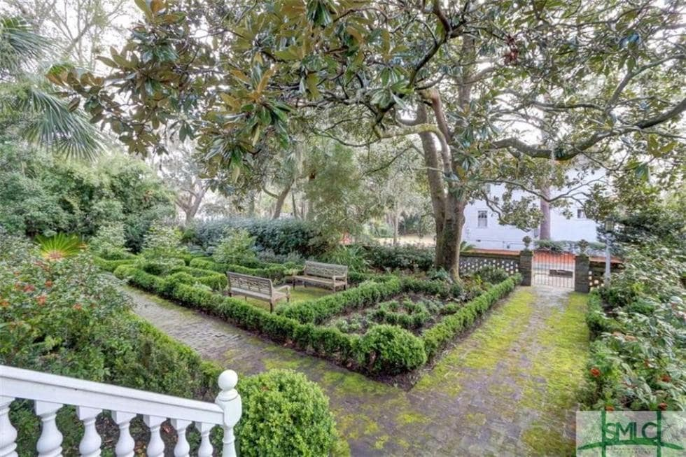 This is a look at the front yard from the vantage of the main entrance. You can see here the gate entry and the shrub garden with a couple of park benches. Image courtesy of Toptenrealestatedeals.com.
