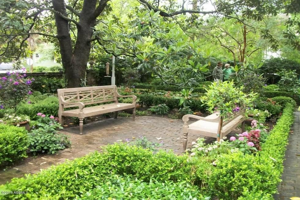 This is a closer look at the couple of the park benches nestled into the shrub garden of the front yard under the shade of tall trees. Image courtesy of Toptenrealestatedeals.com.