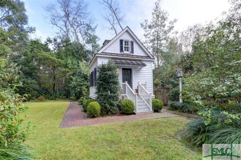 This is the guest house with a the same white exteriors as the main house complemented by the surrounding landscape of shrubs and trees. Image courtesy of Toptenrealestatedeals.com.