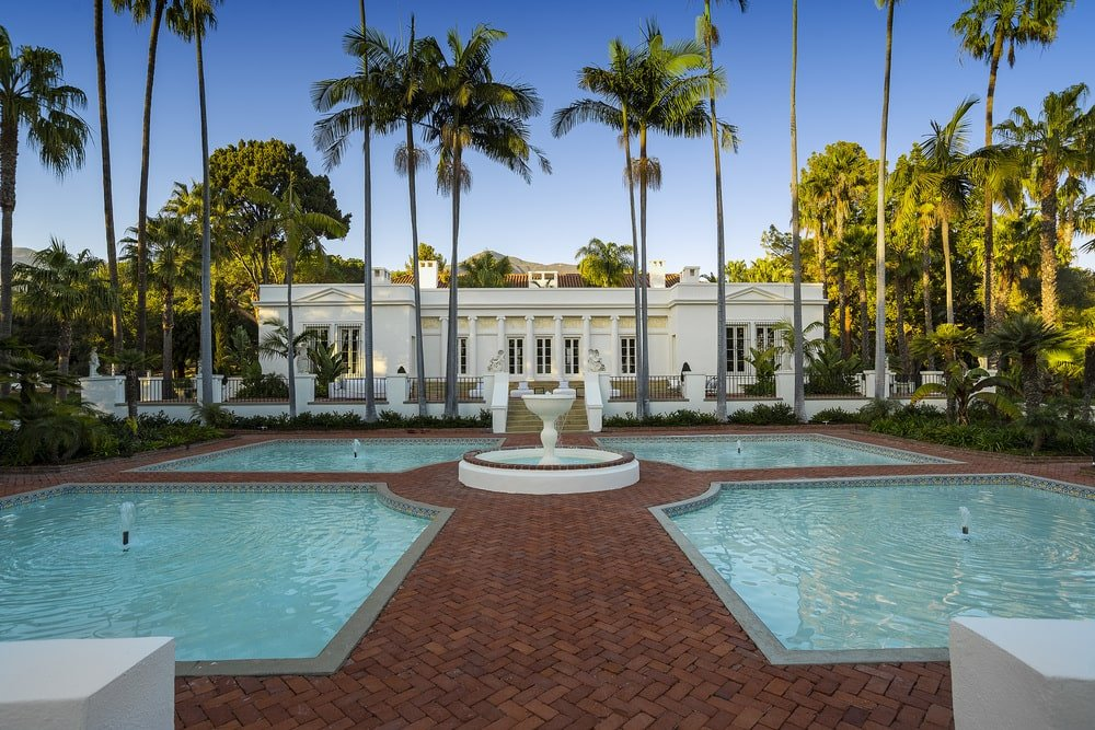 This is a look at the back of the house showcasing the bright beige exteriors, swimming pools with a fountain and tall palm trees. Image courtesy of Toptenrealestatedeals.com.