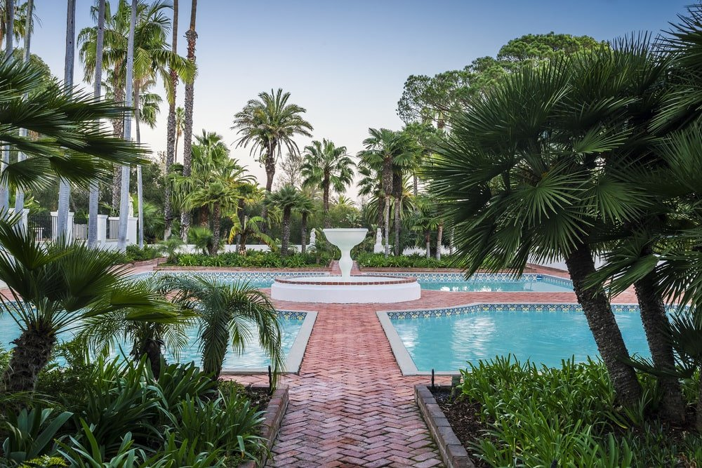 This is a look at the backyard pools surrounding a large fountain. These are then flanked with two sets of Persian gardens filled with shrubs and tropical trees. Image courtesy of Toptenrealestatedeals.com.