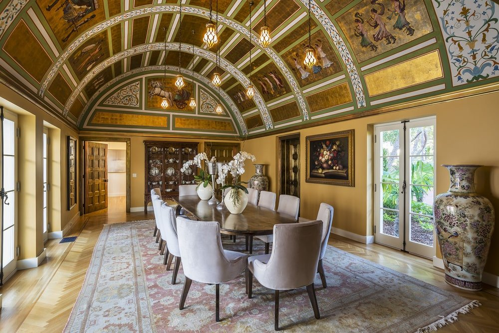 This is the formal dining room that has a long dark wood dining table surrounded by gray chairs. These are then complemented by the cove ceiling that is filled with golden accents and details that tells an ancient story. Image courtesy of Toptenrealestatedeals.com.