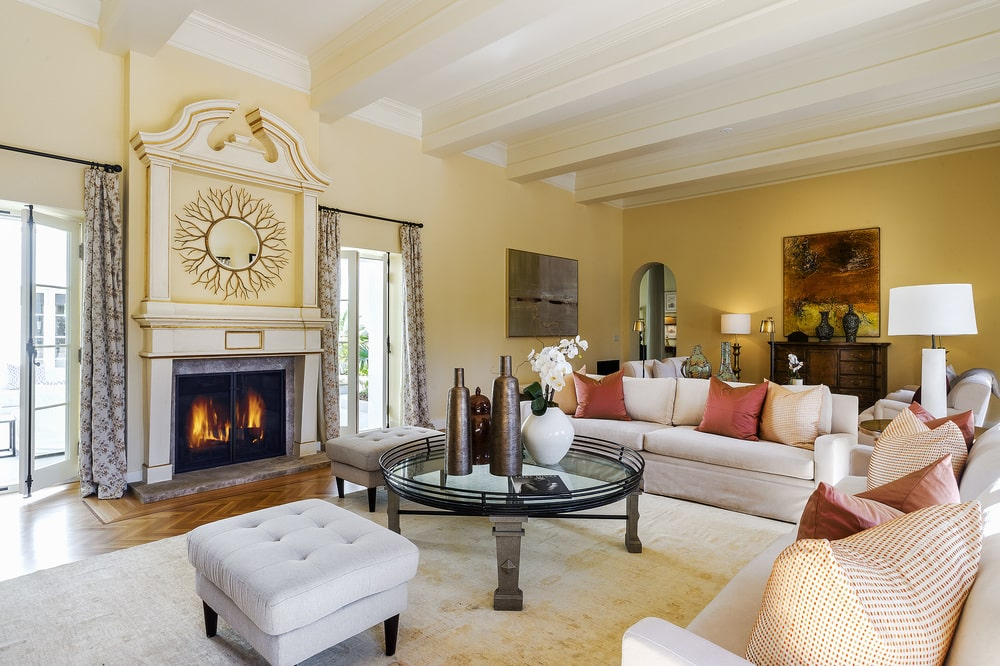 This family room has beige walls, a white beamed ceiling and a large fireplace that warms the light gray sofa set and the glass-top coffee table. Image courtesy of Toptenrealestatedeals.com.