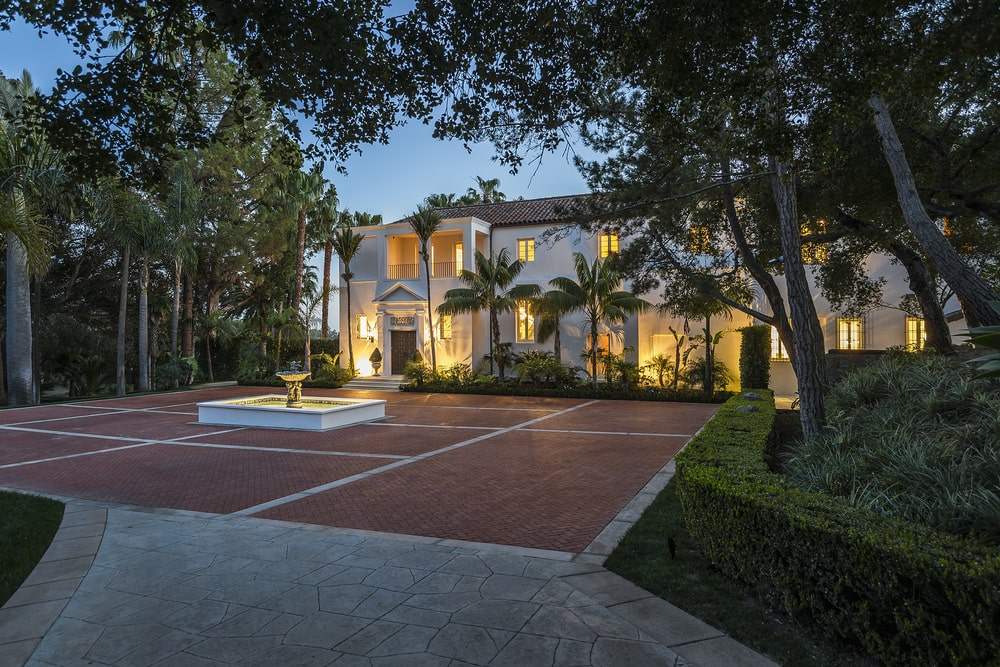This is the front of the house with a large courtyard of terracotta bricks adorned with a large fountain in the middle and bordered with tropical trees. Image courtesy of Toptenrealestatedeals.com.