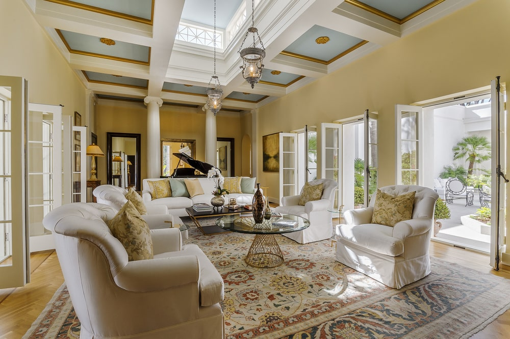 This is the bright and airy living room with a coffered ceiling that has a skylight, beige walls that match the beige sofa set and a set of French glass doors. Image courtesy of Toptenrealestatedeals.com.