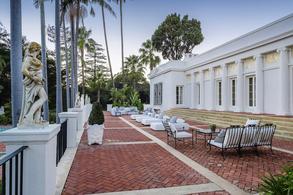 This is a closer look at the back of the house that has a large terrace with red brick flooring fitted with various sitting areas. The bright white outdoor furniture stands out against the terracotta tone of the floor. Image courtesy of Toptenrealestatedeals.com.