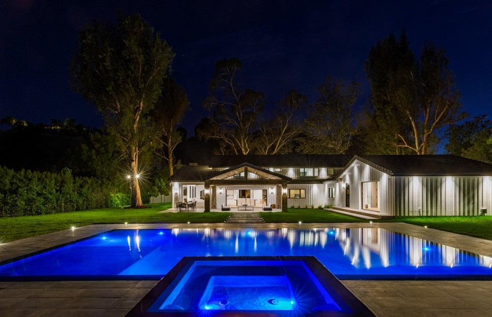 This is a look at the back of the house showcasing the ethereal blue glow of the swimming pool and spa. This contrasts with the warm glow of the house. Image courtesy of Toptenrealestatedeals.com.