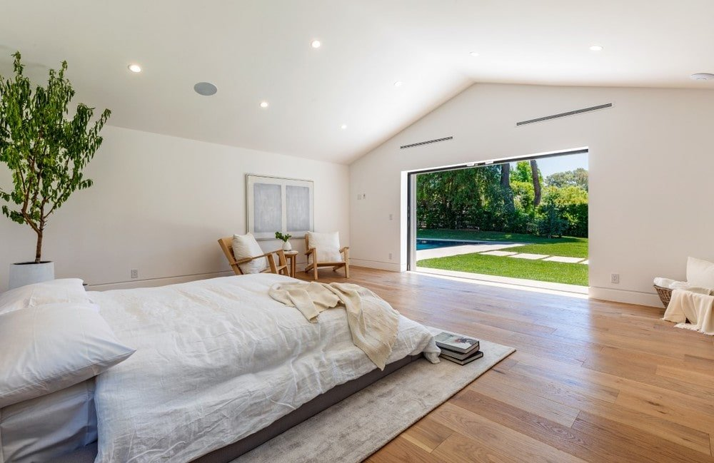 The bedroom has bright beige walls and cathedral ceiling complemented by the hardwood flooring and the open wall on the far side that connects to the backyard. Image courtesy of Toptenrealestatedeals.com.