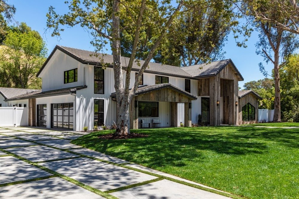 This is a look at the front of the house with bright white exterior walls complemented by the wood-toned elements along with the landscape. Image courtesy of Toptenrealestatedeals.com.