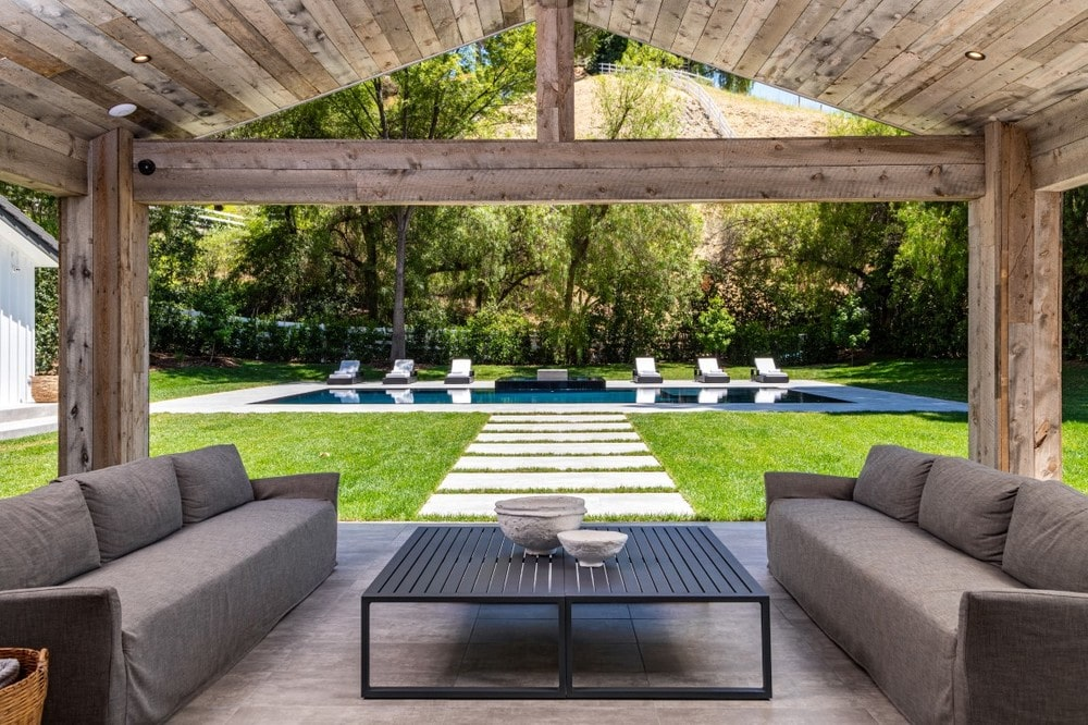 This is the poolside pavilion and covered patio with a couple of gray sofas flanking a black coffee table. Thes eare complemented by the wooden cathedral ceiling and the open walls. Image courtesy of Toptenrealestatedeals.com.