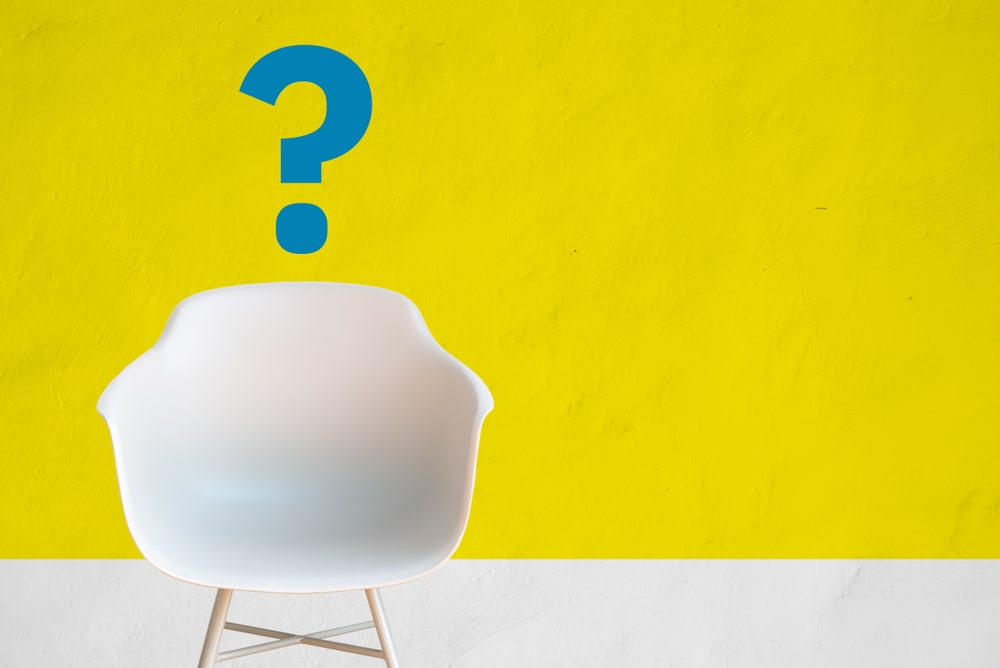 A white modern chair placed against a yellow wall with a blue question mark painted on it.