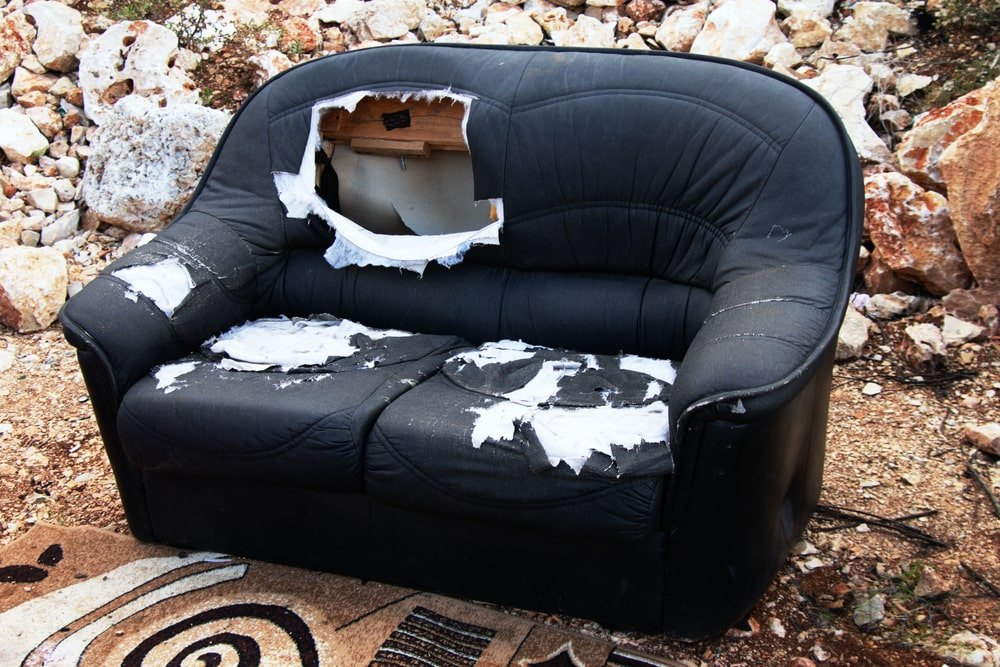 A dumped used black sofa with a large hole on it.