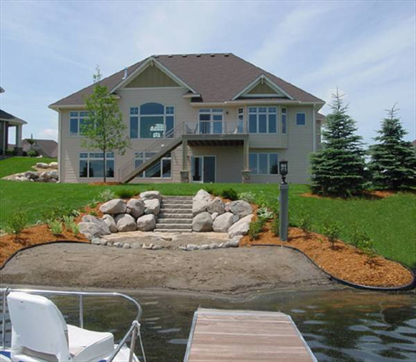 Rear exterior view showing the upper balcony, covered patio, and a stone staircase leading down the lake.