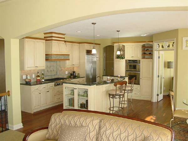 The kitchen is equipped with granite countertops, stainless steel appliances, white cabinetry, and a breakfast island.