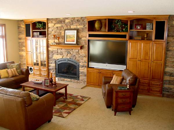 The family room has a stone fireplace, wooden built-ins, and brown leather seats paired with a wooden coffee table.