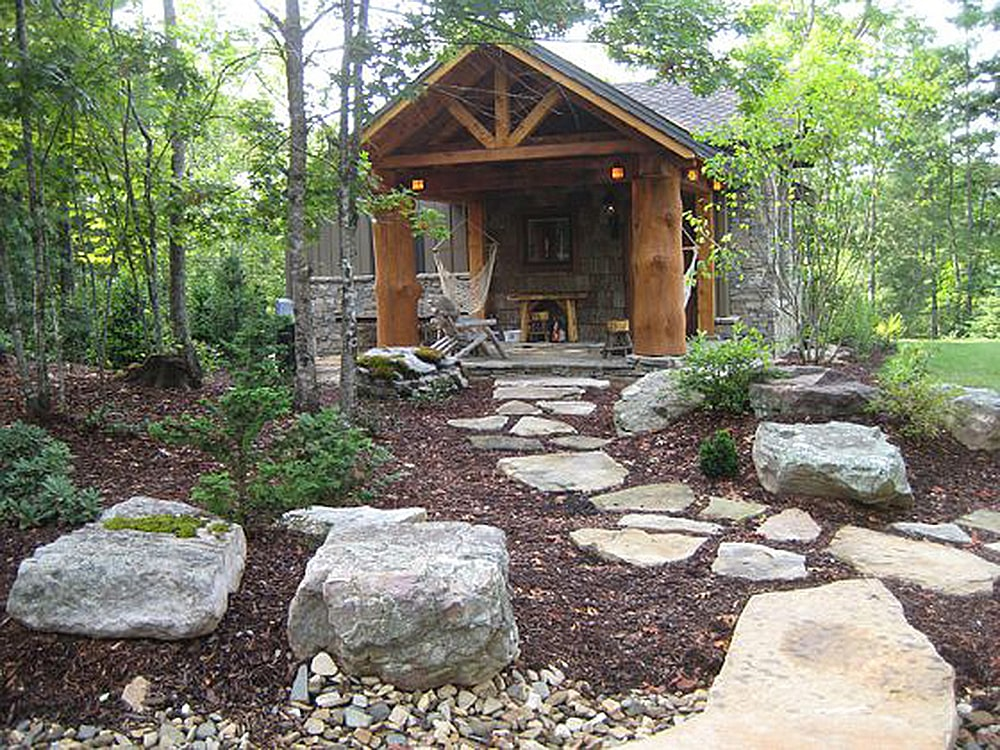 Right exterior view showing the boulders and a stone walkway leading to the covered porch.