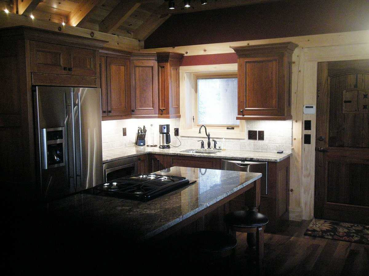 The kitchen has granite countertops, stainless steel appliances, and wooden cabinetry.