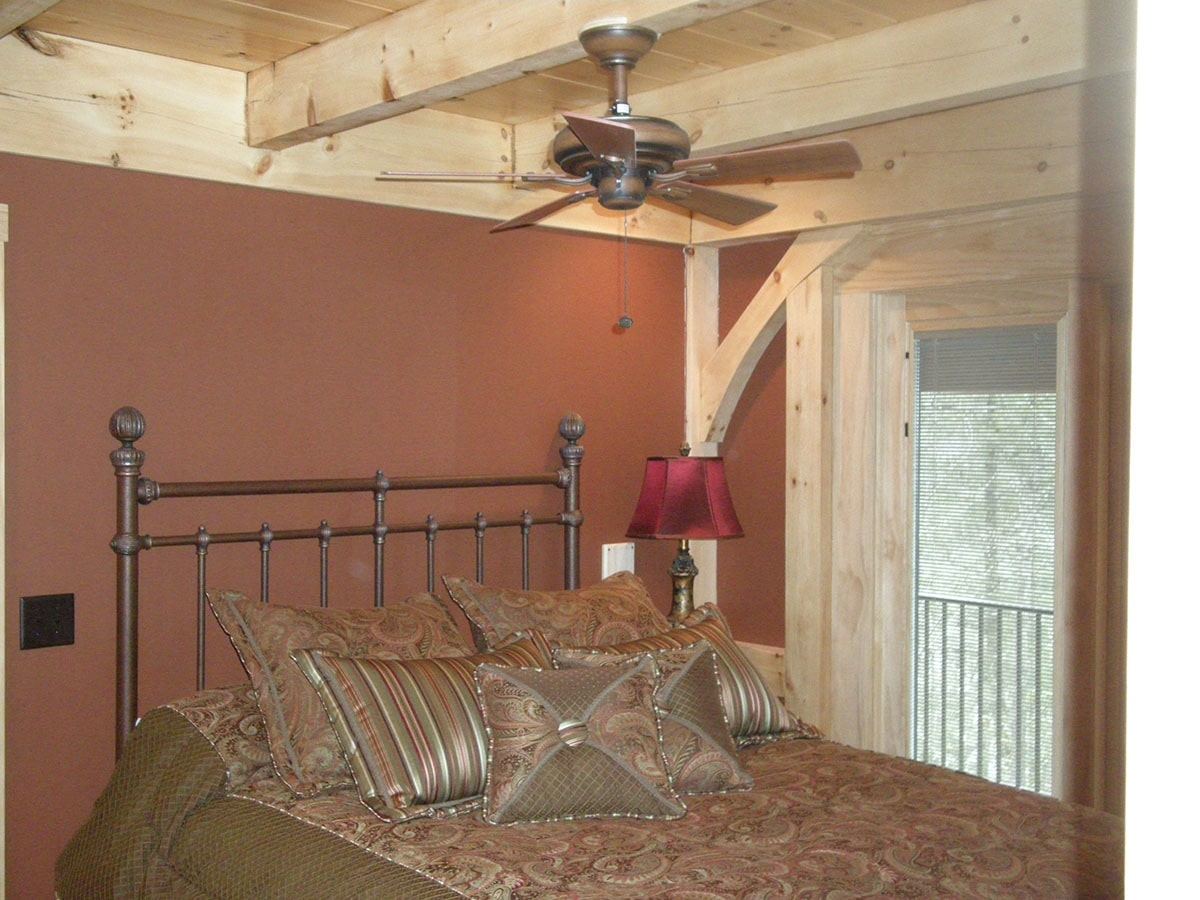 Another bedroom with a metal bed, red walls, and a beamed ceiling mounted with a copper fan.