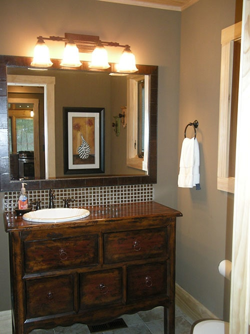 Powder room with a sink vanity placed under the wooden framed mirror and glass sconces.