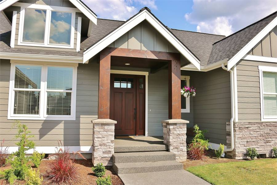 Home entry with a wooden front door guarded by tapered columns.