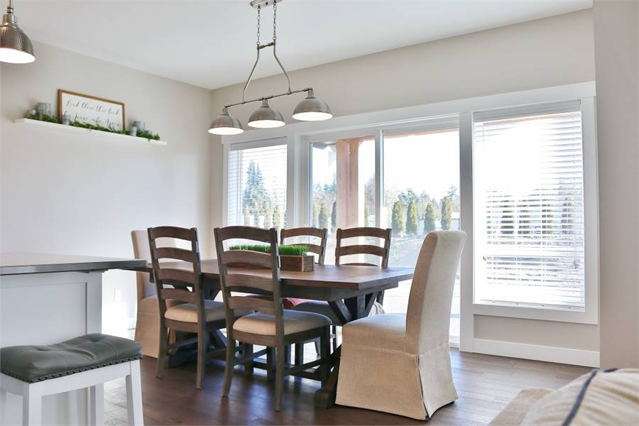 The dining room has cushioned and skirted chairs, a wooden dining table, and chrome dome pendant lights.