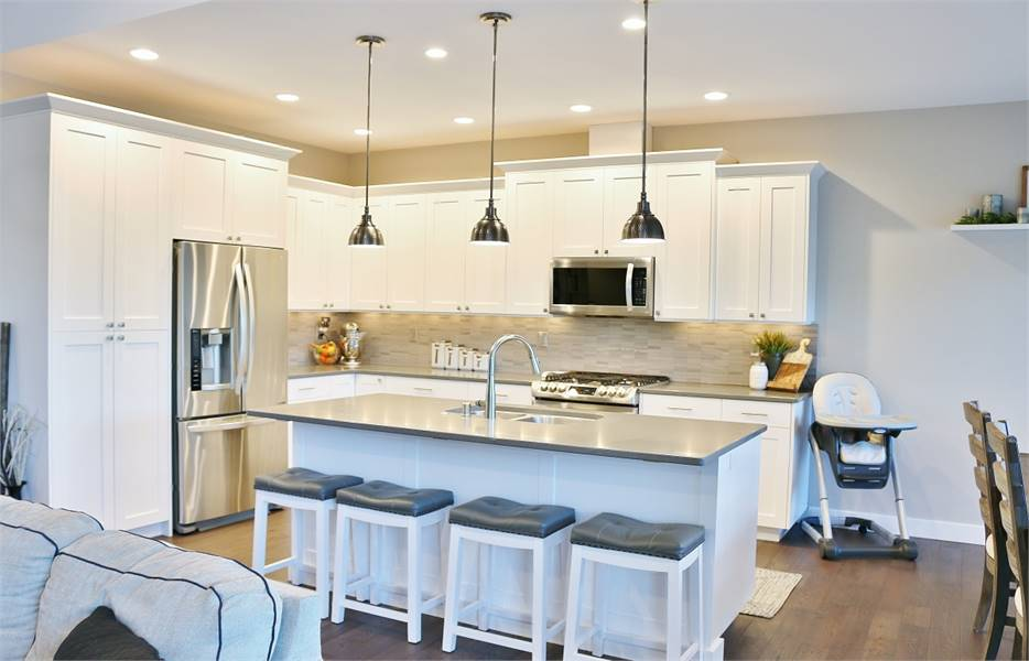Chrome dome pendants and cushioned bar stools complement the kitchen island.