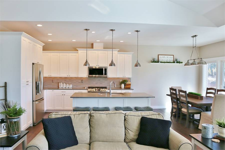The kitchen sits behind the beige sectional that's accentuated with black throw pillows.
