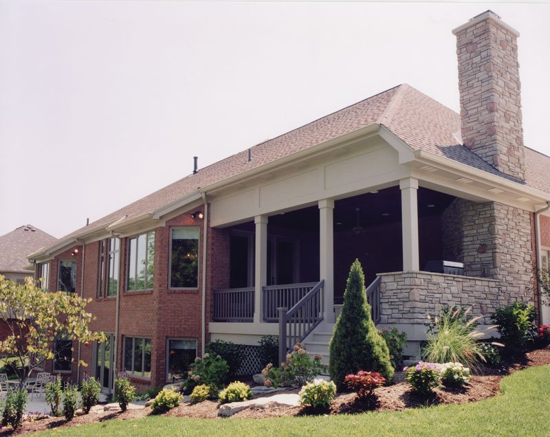Rear exterior view showing the covered deck situated in a sloping lot.