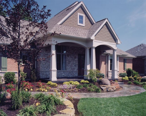 Home entry with a curved walkway and a covered porch lined with tapered columns.