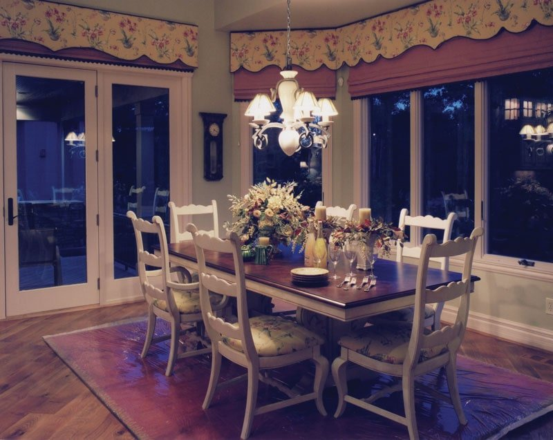 Formal dining room with cushioned chairs, wooden dining table, and a warm glass chandelier.