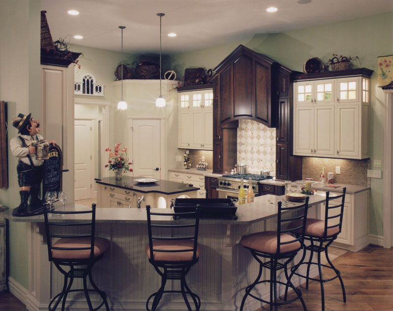 Kitchen with white cabinetry, center island, and a curved peninsula complemented with cushioned counter chairs.
