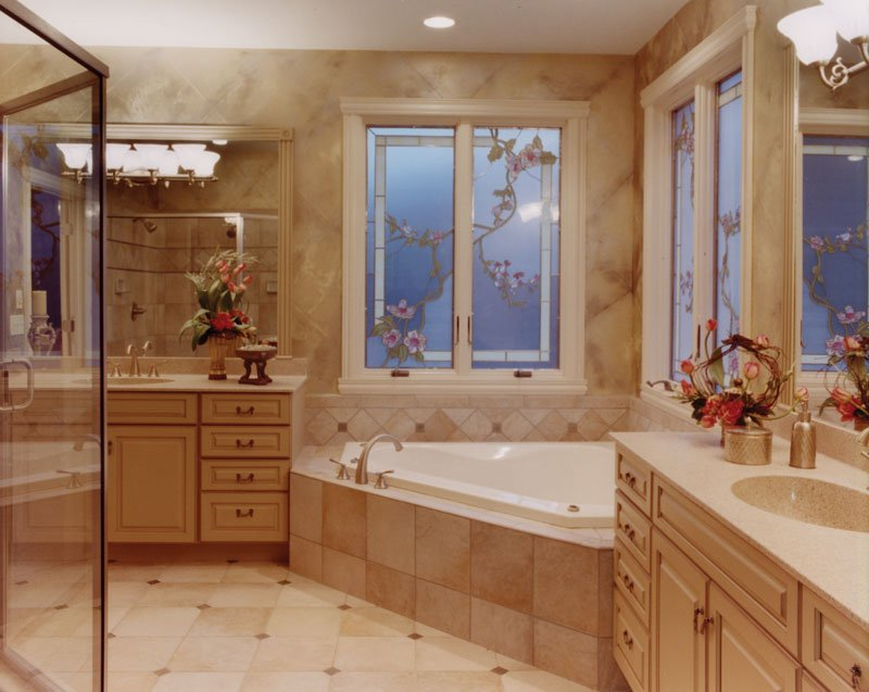 The primary bathroom offers his and her vanities, a corner tub, and a walk-in shower reflected in the mirror.