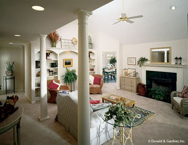 Living room with skirted sofa, cushioned armchairs, arched built-ins, and a fireplace with a mirror on top.