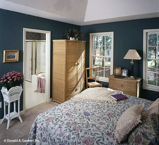 The primary bedroom has a cozy bed, wicker dressers, blue walls, and a high coved ceiling.