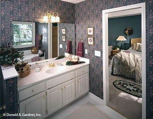 Primary bathroom with floral wallpaper and a white vanity accentuated with brass knobs and fixtures.
