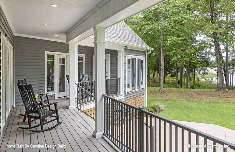 The covered porch is filled with dark wood rocking chairs sitting on a wide plank flooring.