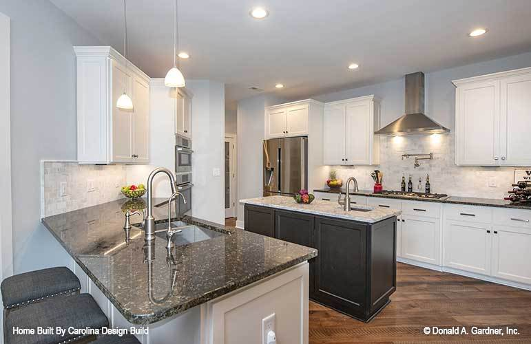 The kitchen has white cabinetry, granite countertops, multiple sinks, center island, and a snack bar.