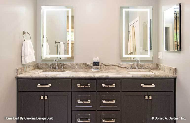 The primary bathroom features a dual sink vanity with granite countertop, dark wood cabinets, and a pair of frameless mirrors.