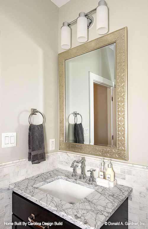 Powder room with black vanity and a decorative mirror illuminated by cylindrical sconces.