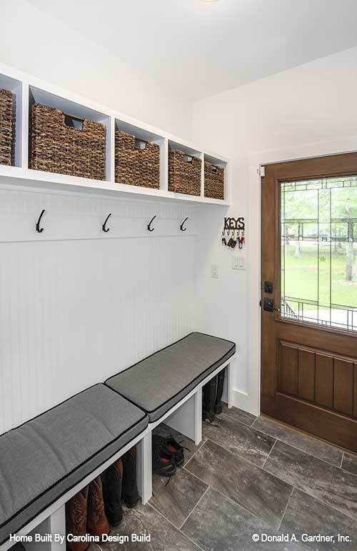 The mudroom has a multi-purpose bench and built-in shelves filled with storage baskets.