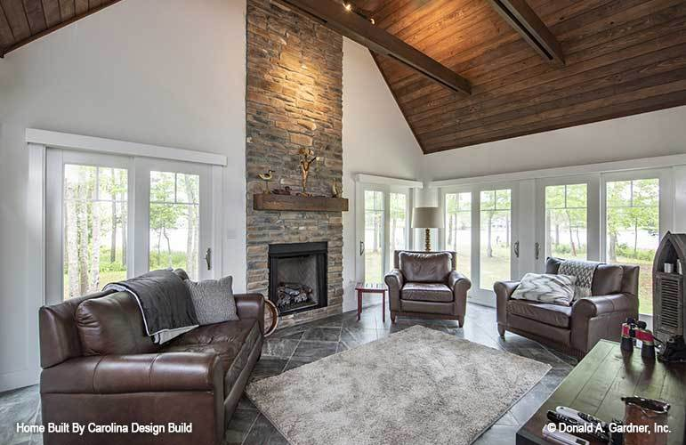 Sunroom with a stone fireplace, leather seats, gray area rug, and a cathedral ceiling lined with exposed beams.