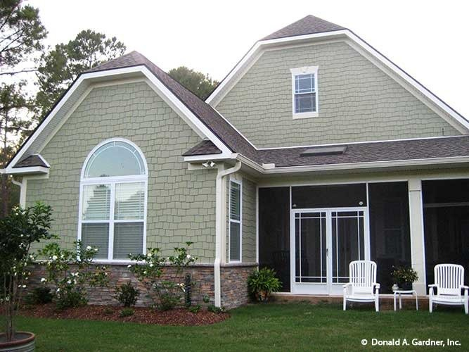 Rear exterior view showing the screened porch complemented with white armchairs.