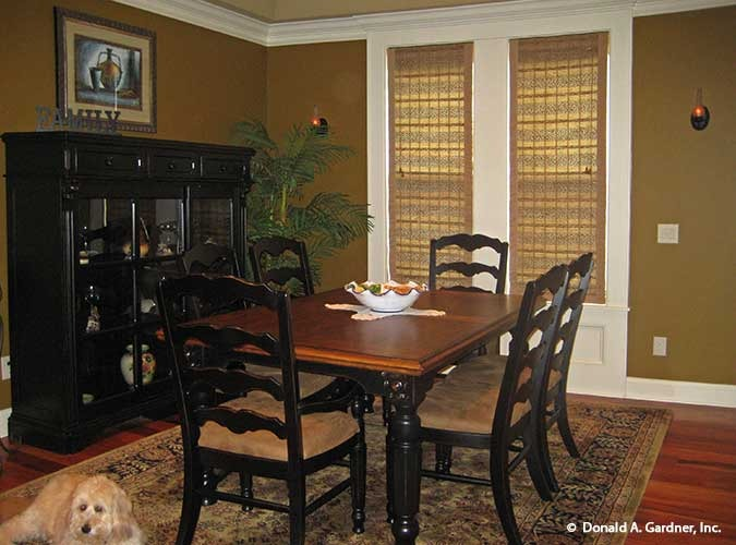 Formal dining room with a black display cabinet, wooden dining table, and cushioned chairs sitting on a vintage area rug.