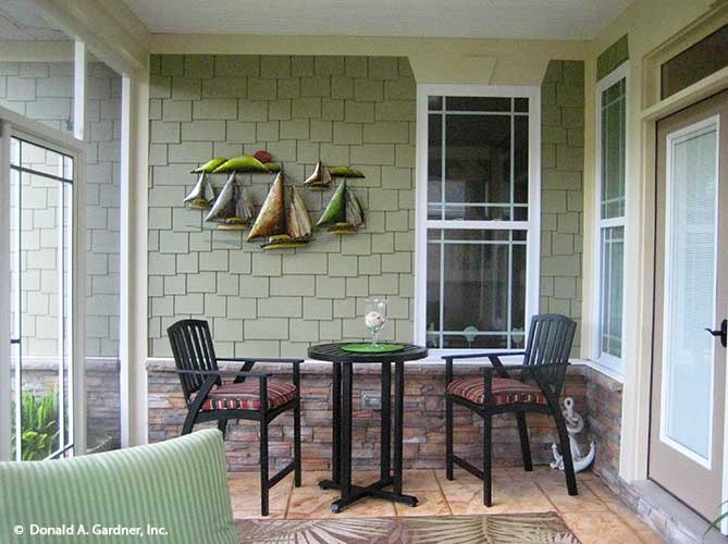 The rear porch is filled with cushioned chairs, a small round table, and ship decors adorning the green brick wall.