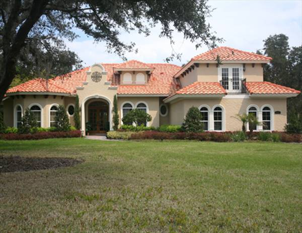 Home facade showing the clay tile roofs, charming dormers, arched windows, and a covered front porch.
