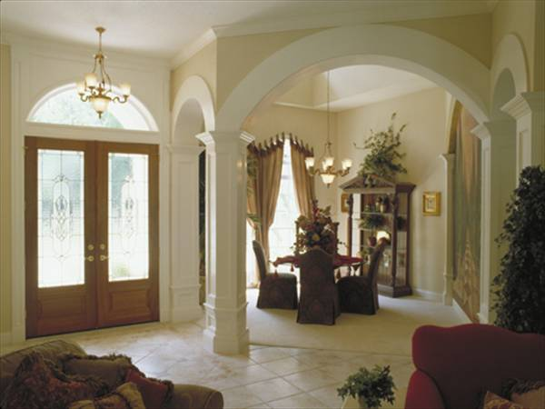 The formal dining room defined with open arches. It has a square table, skirted chairs, and a display cabinet.