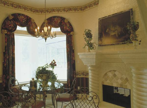Breakfast nook with a fireplace, round glass top table, ornate metal chairs, and a picture window dressed in classy valance and drapes.