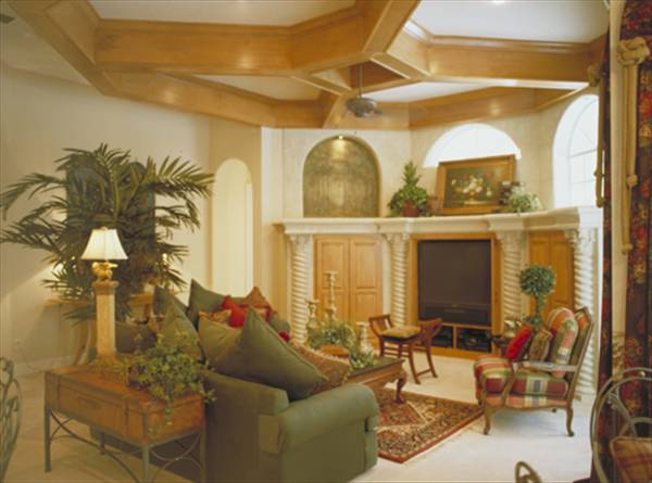 The family room has a stylish coffered ceiling, a TV, a gray sofa, cushioned chairs, wooden tables, and fresh plants.