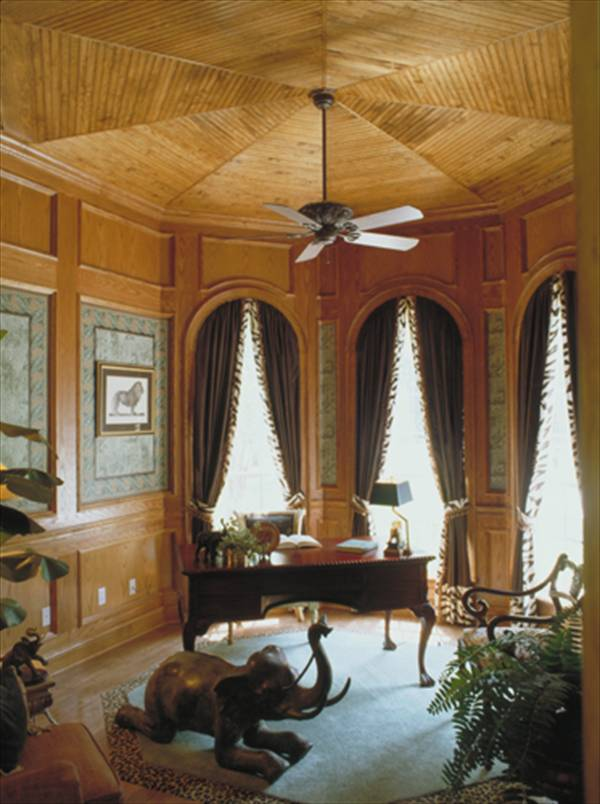 Study with cushioned seats, dark wood desk, elephant statue, and wood-paneled walls that match the circular ceiling.