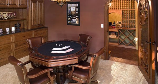 Game room with an octagon poker table, brown leather chairs, and wooden cabinets. An arched door on the side opens to the wine cellar.